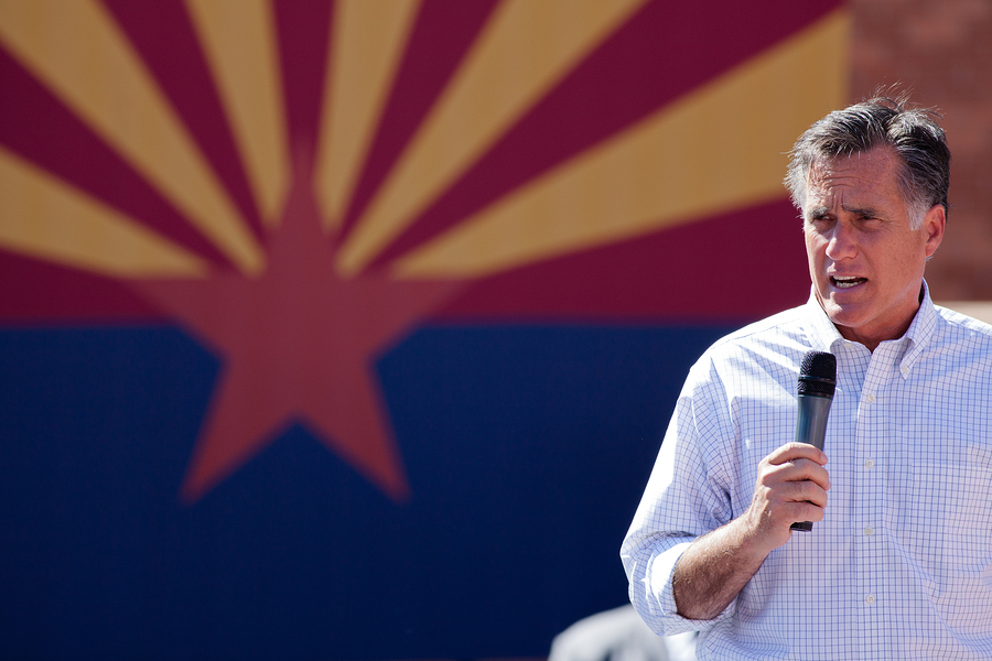 Mitt Romney standing in front of an Arizonan flag.